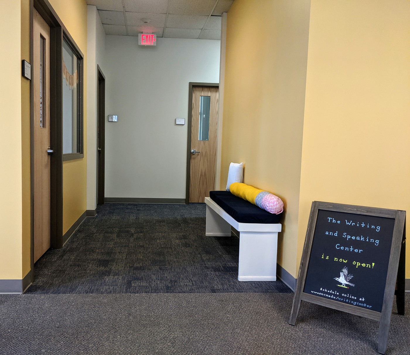 Picture of the entrance to the new Center. There is a white bench, temporary sign, and pale yellow walls.