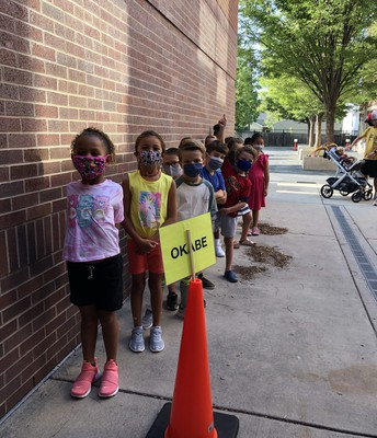 Students practice standing in line outside