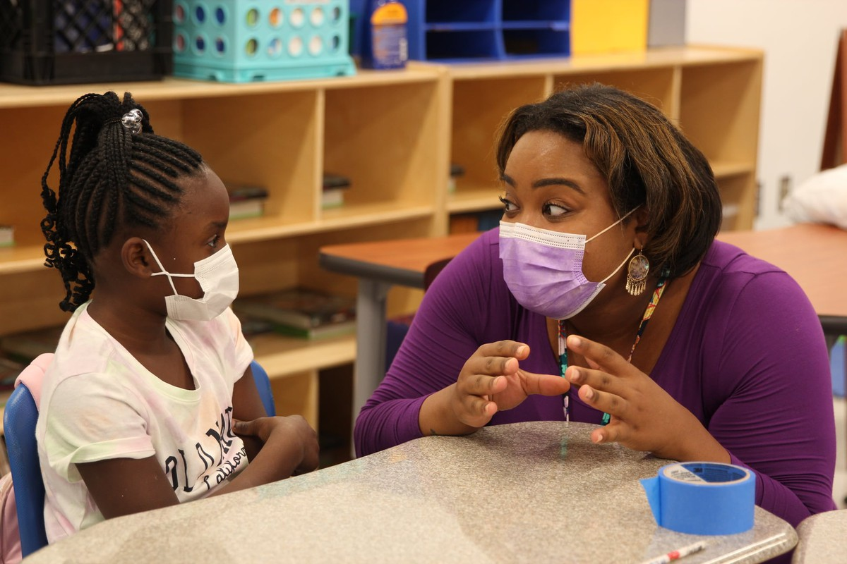 A teacher and a student, each wearing masks, have a conversation in a classroom.