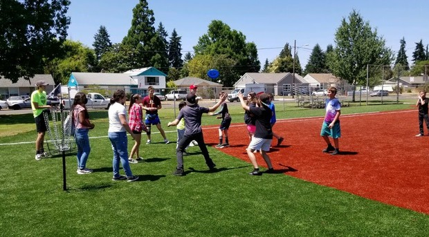 A large group of students playing frisbee golf.