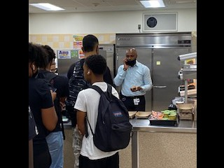 Dr. Haggins serving lunch and handling school business at the same time!