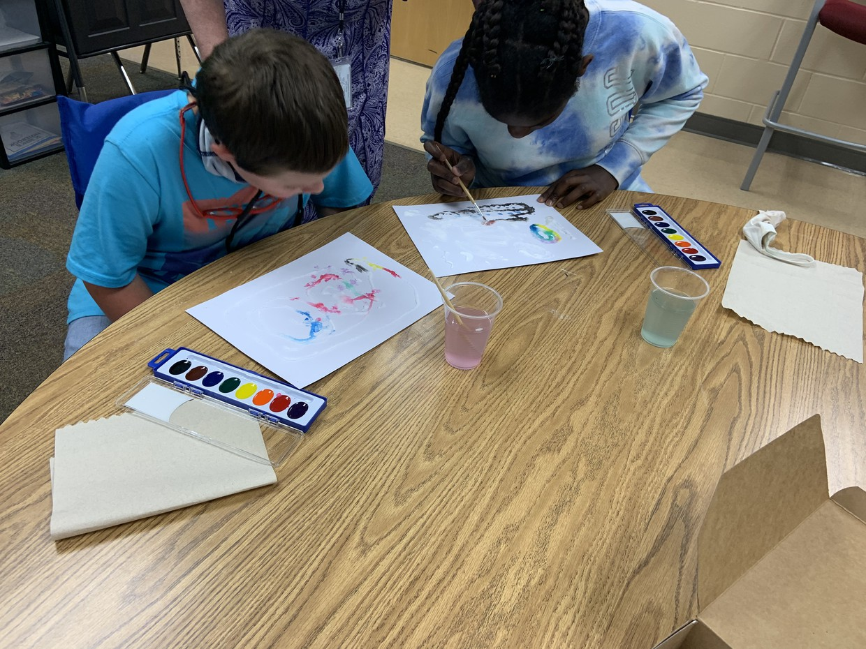 2 students sit at a table; they each have white paper with colorful drawings partially done. Plastic cups of slightly colored water, trays of watercolor paints, and paper towels sit on the table