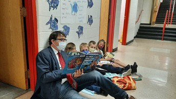 Mr. C sits with Kindergarten students to enjoy a good book