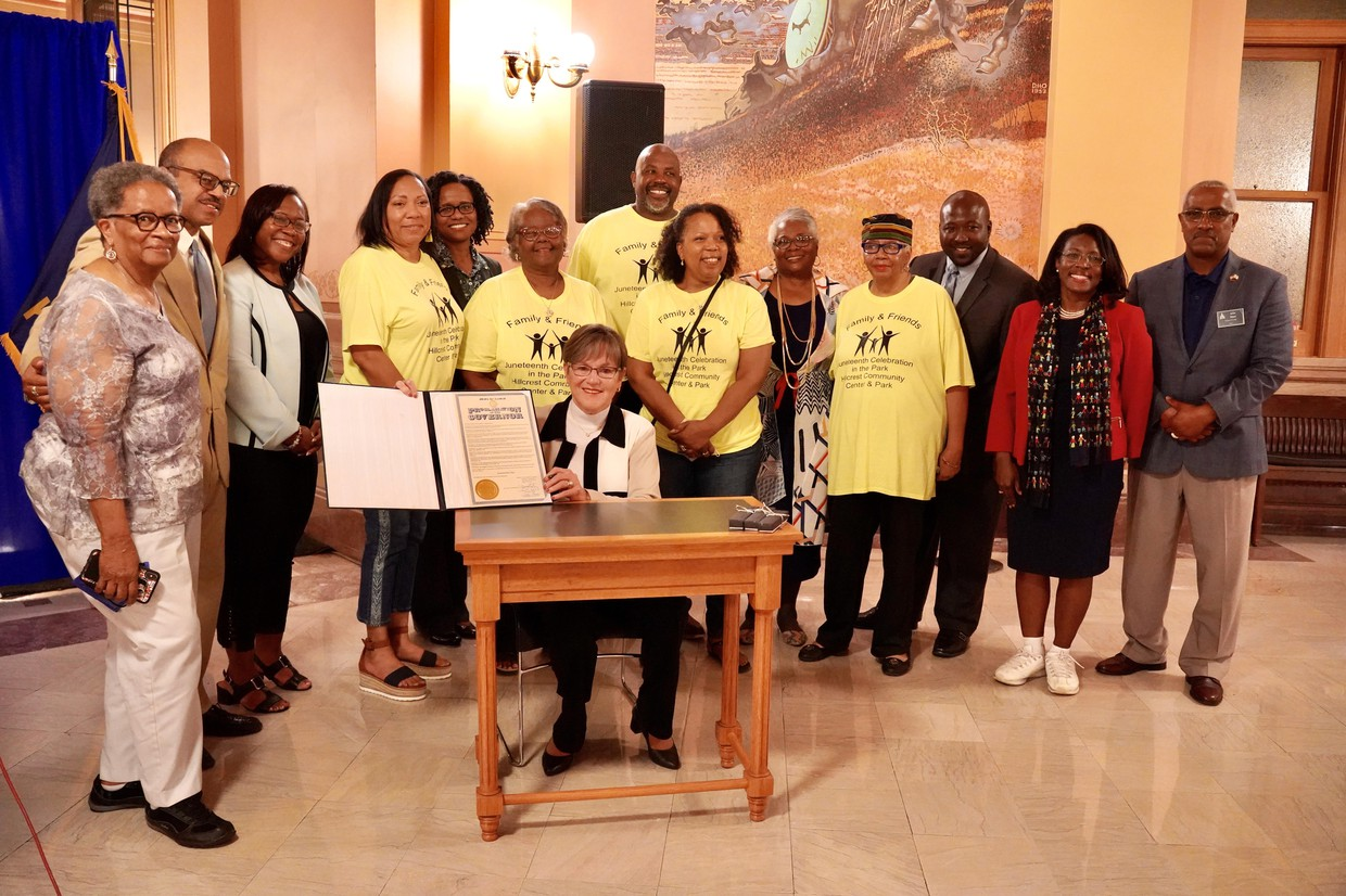 Governor Laura Kelly holds up signed Juneteenth Proclamation surrounded by crowd of supporters
