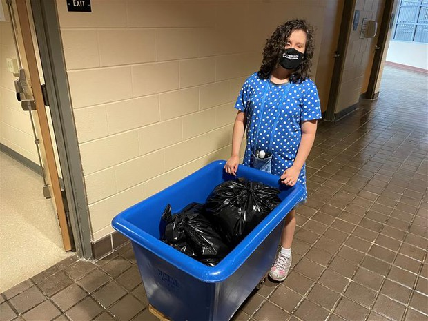 Janna pushing a large, blue bin with several closed garbage bags inside
