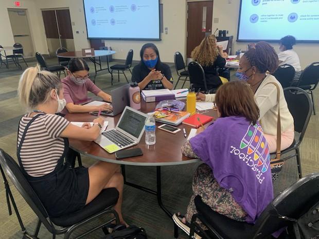 Preschool teachers sit at a round table making conversation
