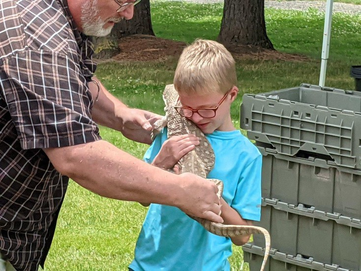 A presenter hands a student a large lizard.
