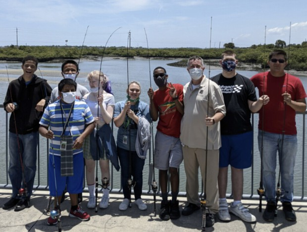 A group of senior students stand with fishing rods in their hands with the intracoastal river behind them
