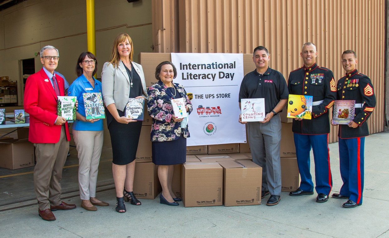 VIPs from the Tournament of Roses, UPS, U.S. Marines, and the Pasadena Unified School District hold some of the 14,000 books being donated to PUSD elementary school children.
