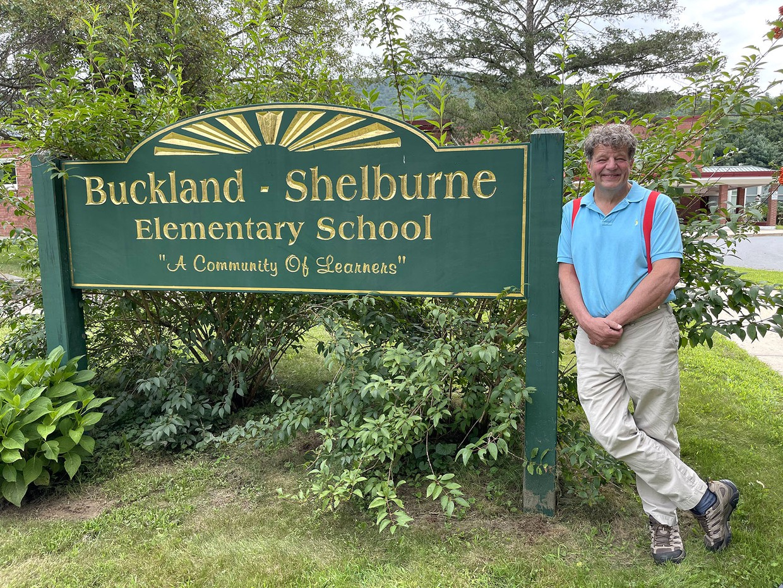 photo of joseph moynihan leaning against Buckland-Shelburne Elementary sign, smiling, outside school building