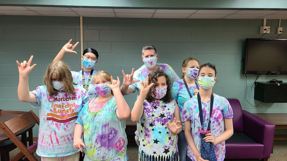 Several girls stand in a group shot while wearing their tie-dye garment creations; they are holding their hands up in the ASL sign for I Love you.