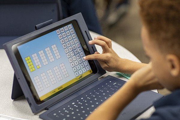 A student works out a math problem on his iPad