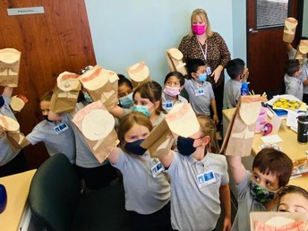 Kindergarten visits the principal's office with their St. Francis puppets