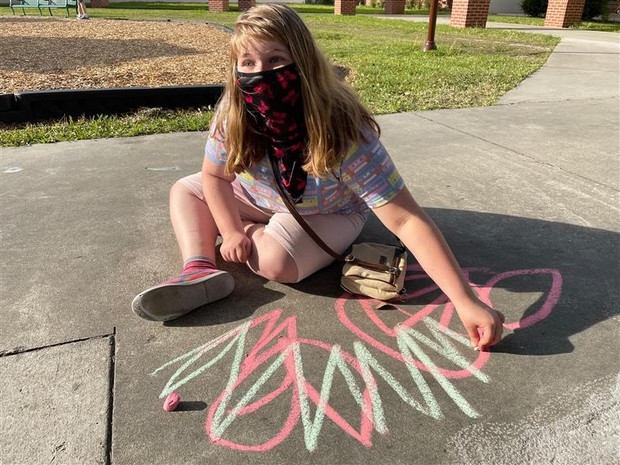 Lillyanna sits on sidewalk with a bold chalk drawing in front of her; a piece of chalk is in her hand