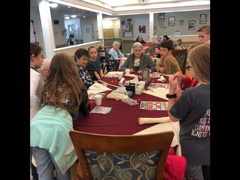 Students playing bingo with residents.