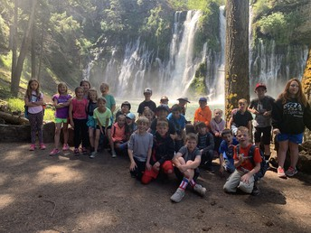 3rd graders posing for a picture with the falls behind them