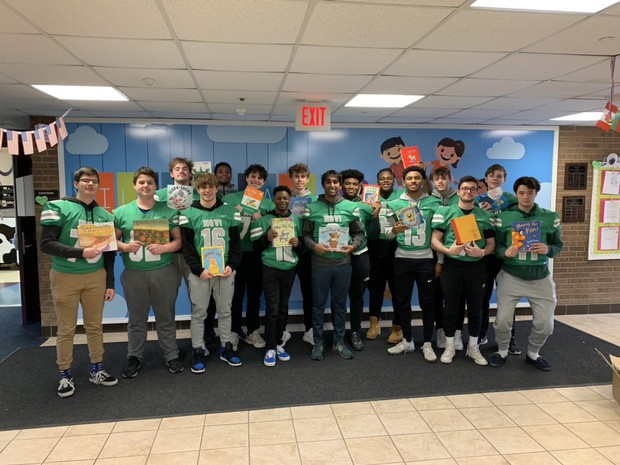 NHS football players holding books