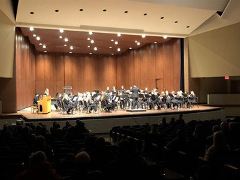 "Mr. Peterson directs Wind Symphony's performance of ""Genesis"""