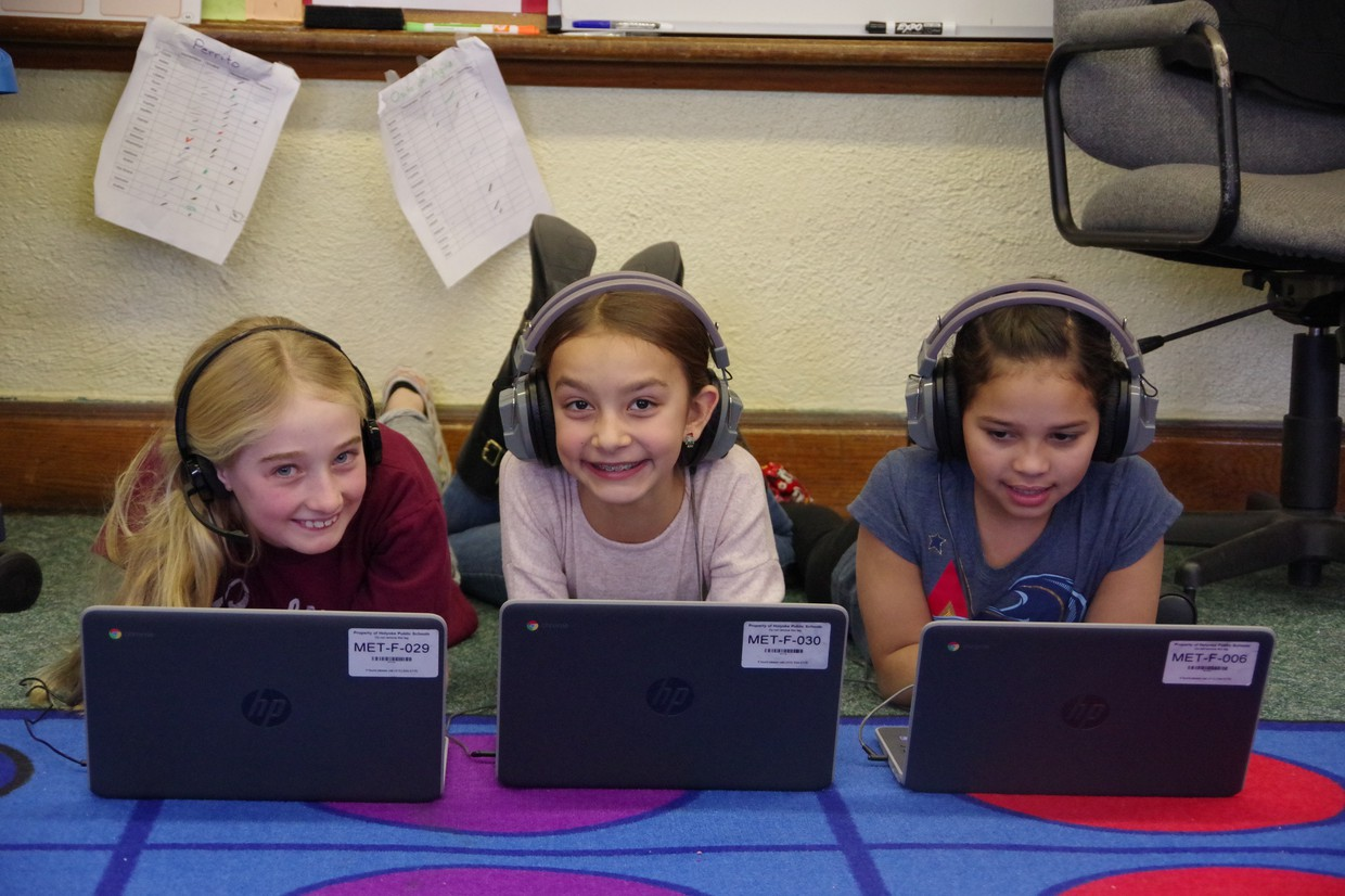 Three elementary school girls working on happily working on laptops in their dual language class.