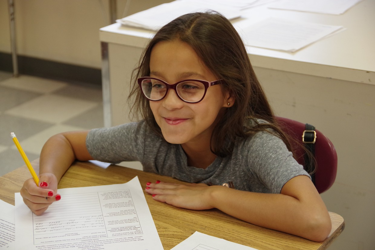 Enroll now! Girl wearing glasses, seated at a desk holding a pencil.