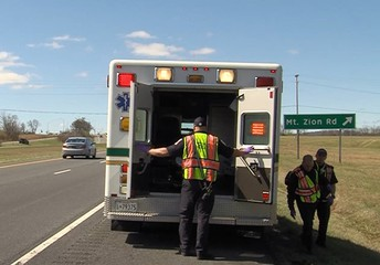 Image shows an ambulance stopped along a highway.