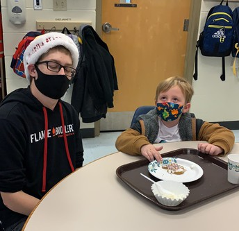 High schooler Thomas assists elementary schooler Kessler decorate his gingerbread man cookie