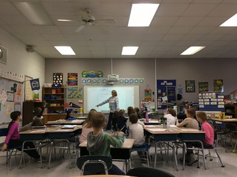 Mrs. Martin models what 1st graders are doing in Daily 5!