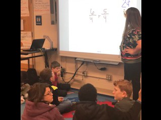 Ms. Nimmons was engaging her students in a conversation on how to add fractions with like denominators.