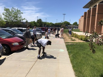 Students from Sports Lit draw chalk murals in front of LMC