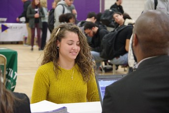 Senior talking to a college rep at the MCAC event