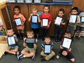 Kinder working on writing using their ipads