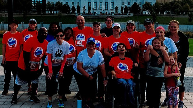 A group photo of OSSB staff and families before the 2017 Spirit Sprint 5k. Many people in the photo are wearing a bright orange shirt with the Spirit Sprint 5k logo.