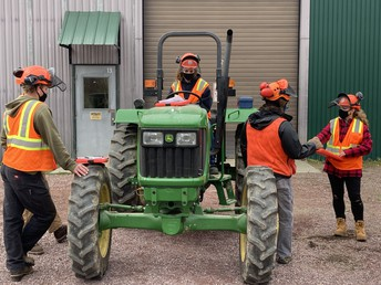 Natalie inspecting a tractor for safety and proper use.
