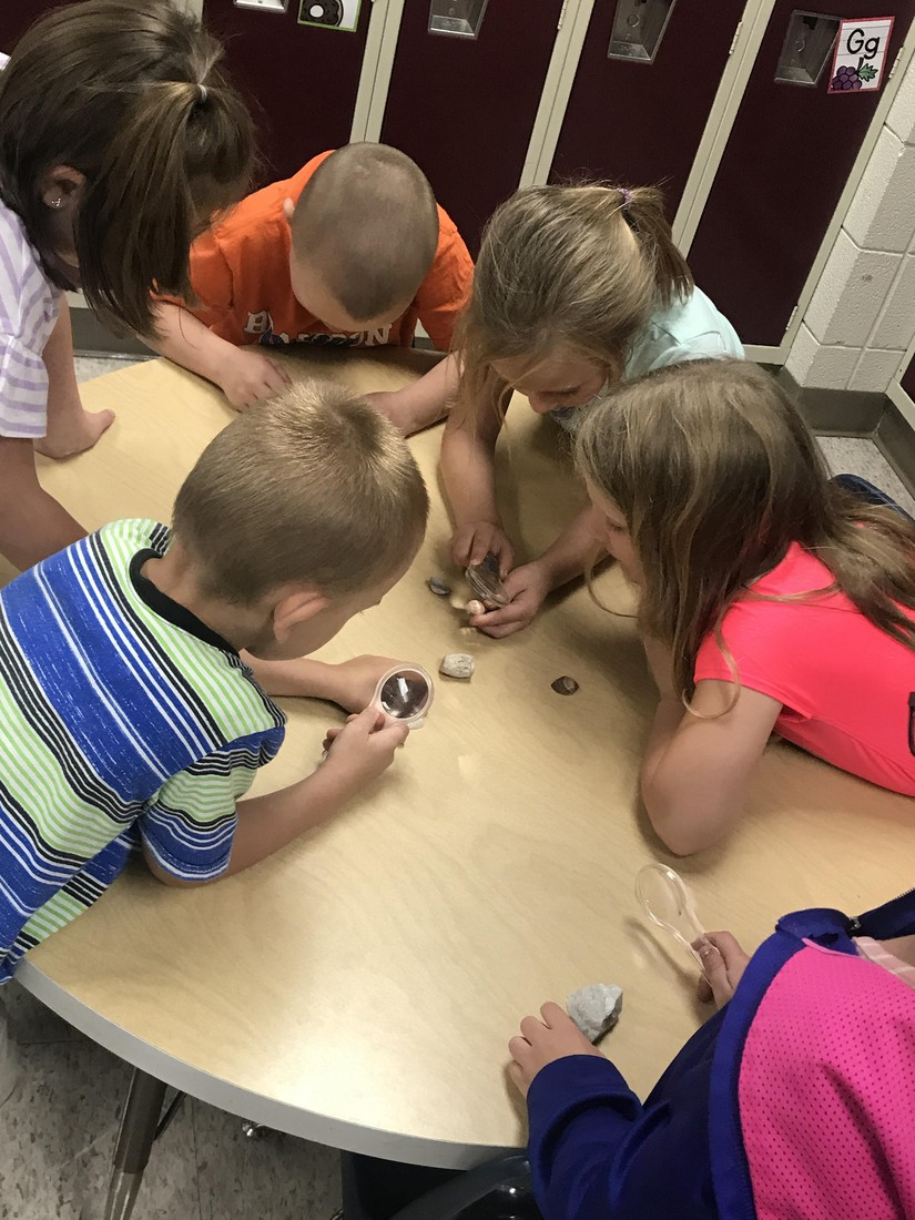 During science, kindergarteners use magnifying glasses to observe seashells and rocks.