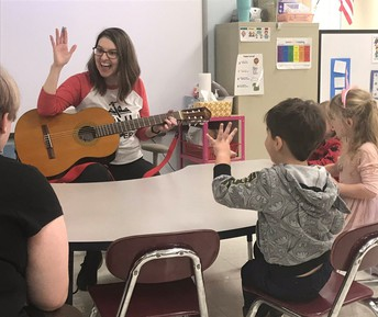 CHS senior Hannah Holbert (far left) assists with Miss Carol's music class at Tiny Toppers Preschool.