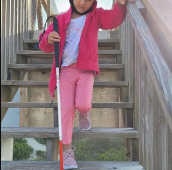 Brianna walking down wooden stairs while using her cane