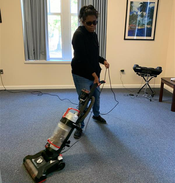 Student is vacuuming the blue carpet floor