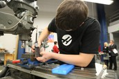 Student working with the manual mill on a project in Precision Machining