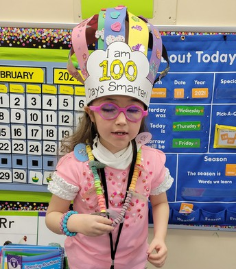 McKenzie wearing 100 beads on a necklace and constructed hat saying I am 100 days smarter.