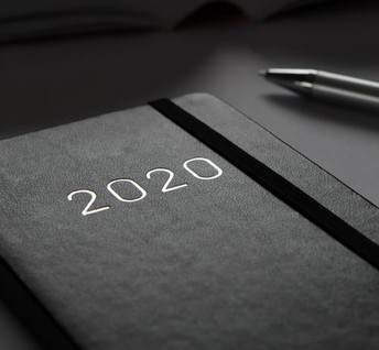Silver pen beside a Black 2020 Date Book