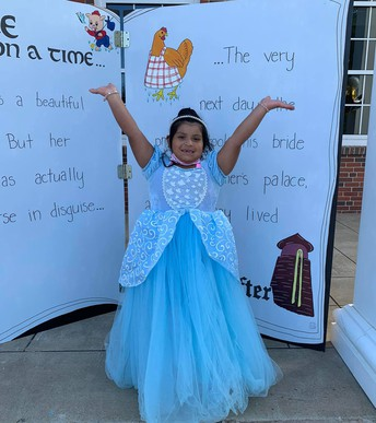 Student in ballgown in front of fairy tail book