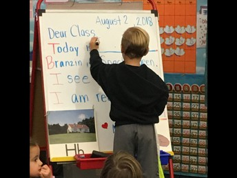 Reading the morning letter in Kindergarten and writing what day of the week it is.