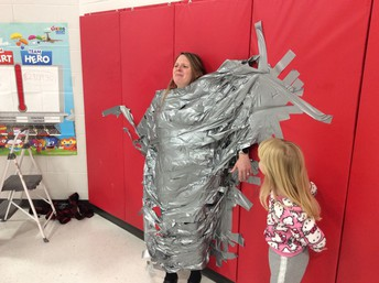 Picture of Principal Simms duck taped to the wall on reward day.