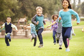 photo of children running through green grass