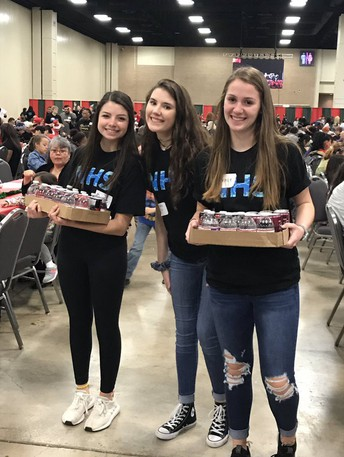 image of national honor society students carrying boxes of food at h-e-b feast of sharing