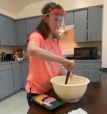Student is stirring ingredients in a large white bowl; a large bag of shredded cheese lies on the table beside her