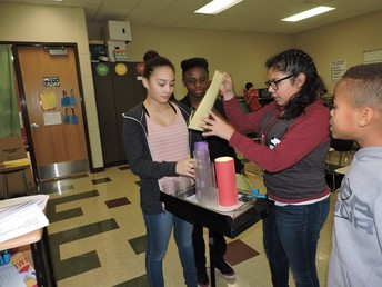 Students standing up, performing experiment with paper tubes