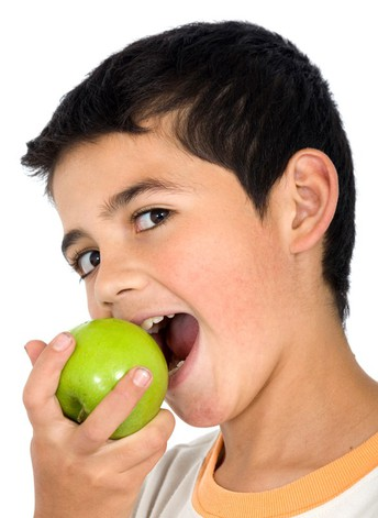 Young boy biting into apple