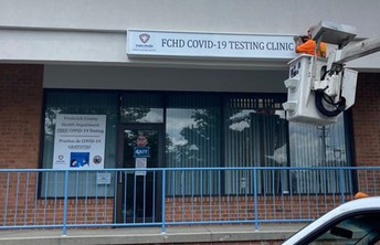 Image shows a man installing a sign over the Frederick County Health Department's Golden Mile testing clinic.