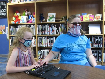 Maely and Bailey sit at a talbe in the library. Both are using their fingers to feel the refreshable braille on a Braille Note device